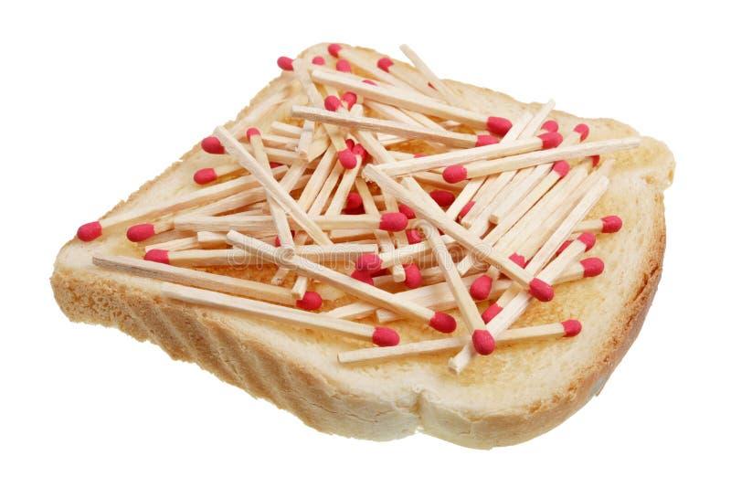 Concetto pericoloso dell'alimento - panino del pane tostato con le partite di legno isolate immagine stock libera da diritti