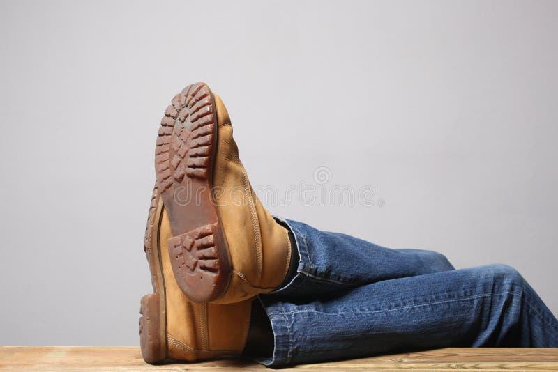 Concetto pigro della persona: le gambe dell'uomo che portano le blue jeans degli stivali di deserto riposano su una tavola di leg fotografie stock