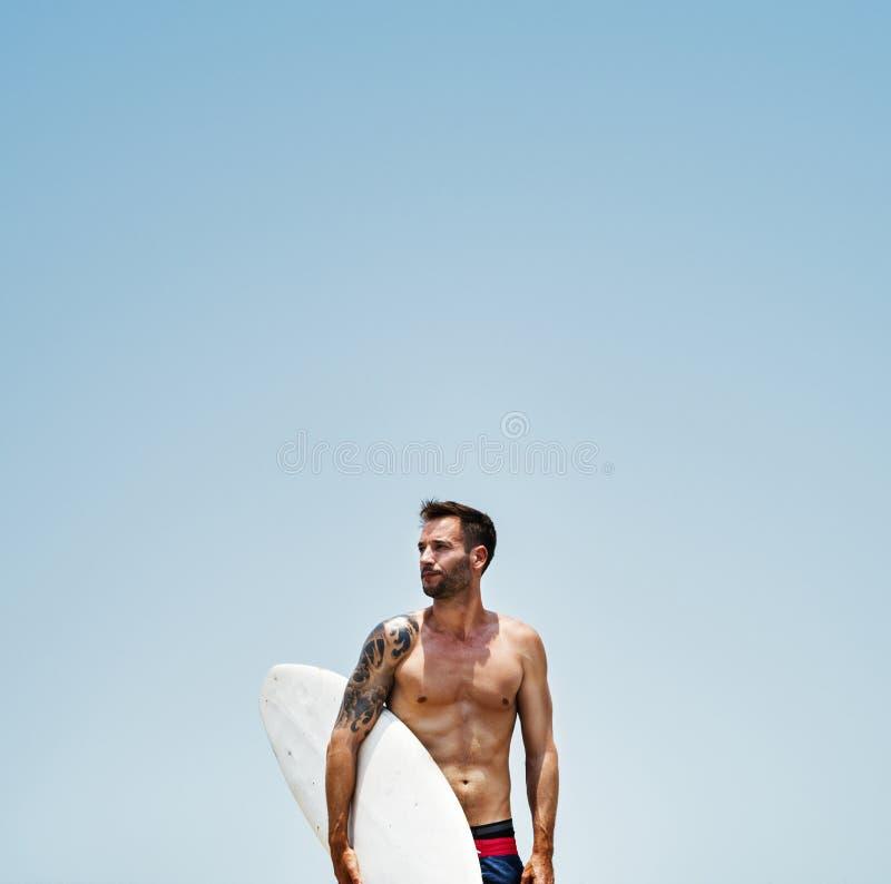 Concetto praticante il surfing della spiaggia di hobby dell'uomo fotografia stock libera da diritti