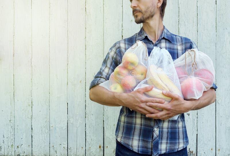 Concetto residuo zero di acquisto Uomo dei pantaloni a vita bassa che tiene le borse riutilizzabili di eco con la frutta fresca P fotografie stock