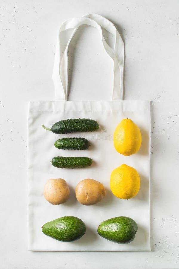 Concetto residuo zero Sacchetti della spesa ecologiical del tessuto con la frutta e le verdure su fondo bianco immagini stock