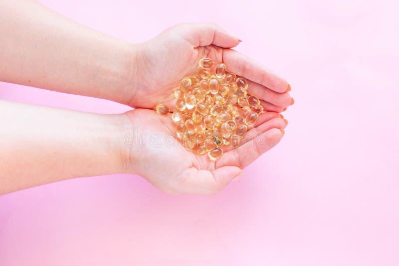 Concetto sano di cibo Una manciata di Omega tre capsule dell'olio di pesce in mani femminili su una vista superiore del fondo di  immagini stock