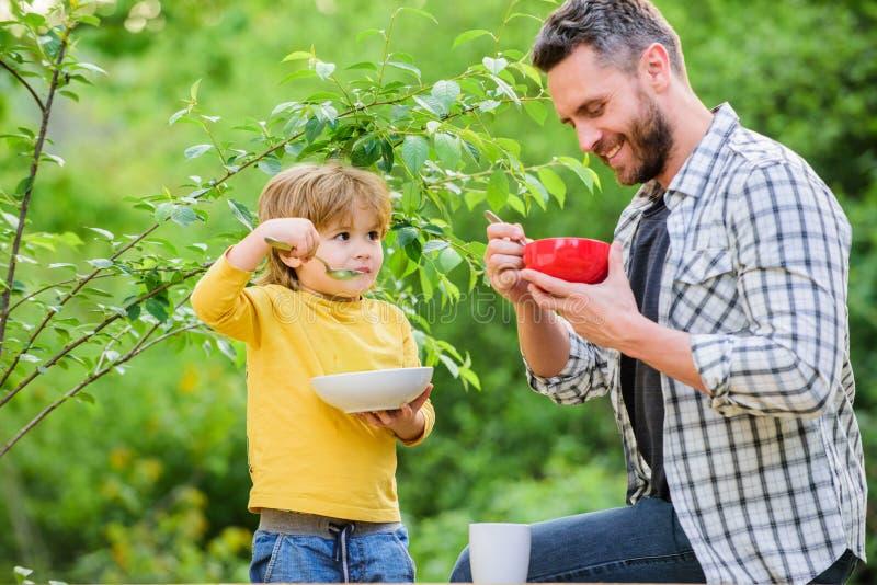 Concetto sano di nutrizione Abitudini di nutrizione La famiglia gode del pasto casalingo Figlio in buona salute del padre della p fotografia stock
