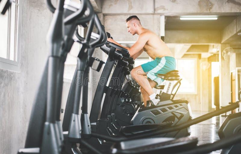Concetto sano di stile di vita, allenamento dell'uomo di sport con il centro dell'interno facente di riciclaggio di cardio addest immagini stock