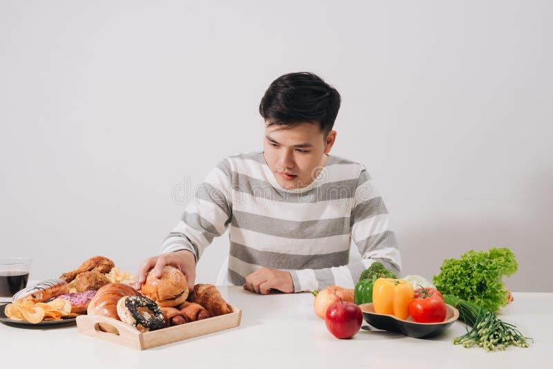 Concetto sano di stile di vita - giovane sorridente che confronta alimento sano e non sano ortaggi freschi ed hamburger fotografia stock