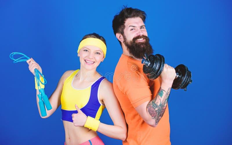 Concetto sano di stile di vita Uomo e donna che si esercitano con la corda di salto e della testa di legno Esercizi di forma fisi fotografia stock libera da diritti