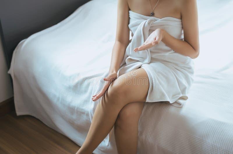 Concetto sano e pelle, donna che applica crema d'idratazione sulla sua gamba fotografia stock libera da diritti