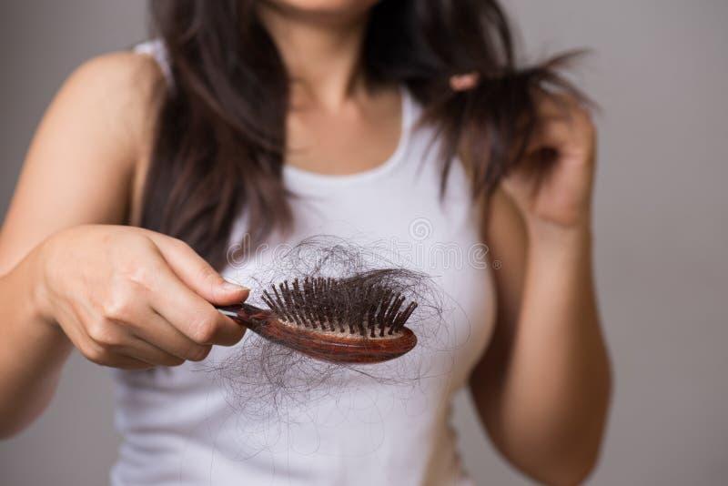 Concetto sano La donna mostra la sua spazzola con i capelli lunghi di perdita e l'esame dei suoi capelli fotografia stock