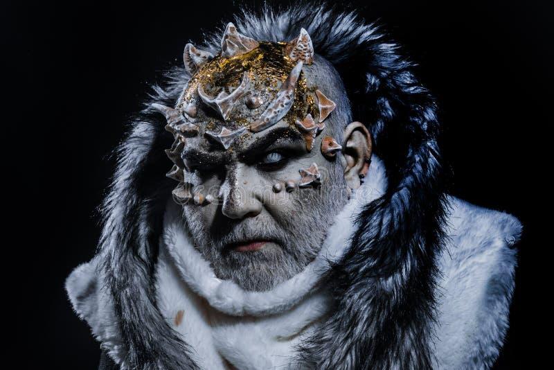 Concetto scuro di arti L'uomo senior con la barba bianca si è vestito come il mostro Demone su fondo nero, fine su Uomo con immagine stock libera da diritti