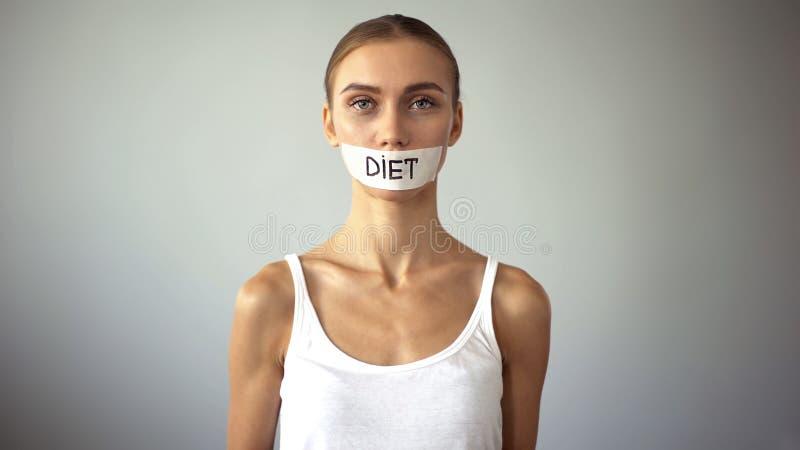 Concetto sfibrante di dieta, donna esile misera con la bocca legata che esamina macchina fotografica immagini stock libere da diritti