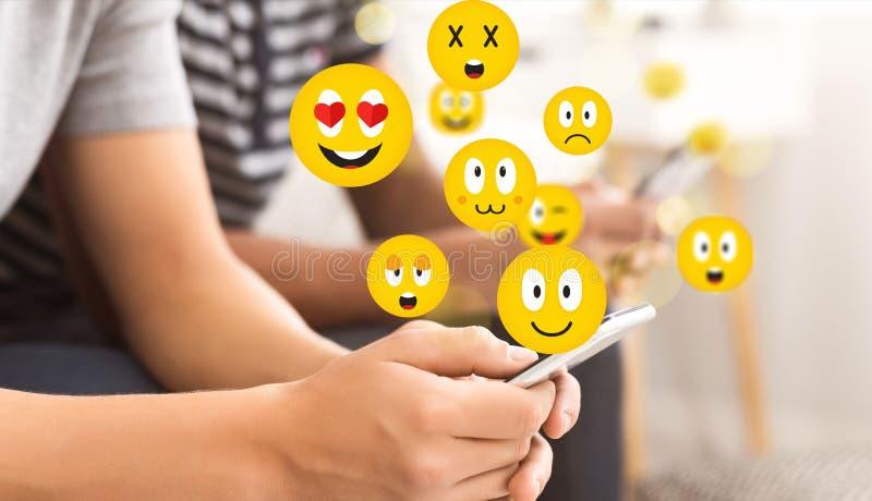Concetto sociale Tipo teenager che per mezzo dello smartphone che invia i emojis fotografie stock