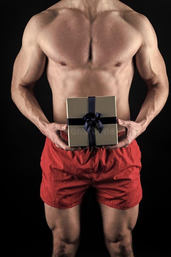 Concetto a sorpresa Torso muscolare di Macho in posa con scatola regalo Babbo Natale per le ragazze adulte macho atletico fotografia stock