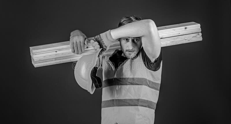 Concetto stanco del lavoratore Uomo nella pulitura dei guanti protettivi e del casco sudata dalla fronte, fondo blu carpentiere immagini stock libere da diritti