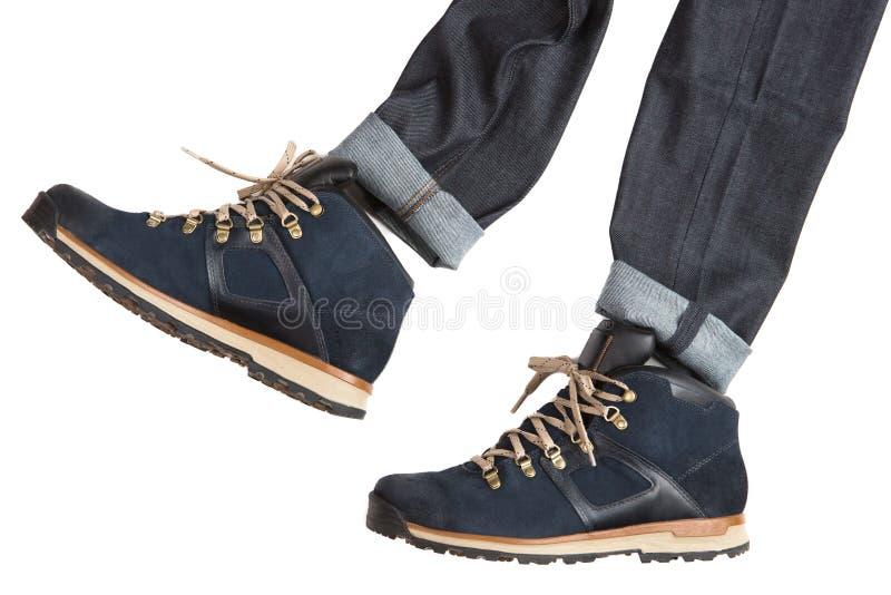 Concetto, stivali blu di autunno e pantaloni neri, come se un uomo stia camminando, intraprendenti un'azione, su un fondo bianco fotografia stock
