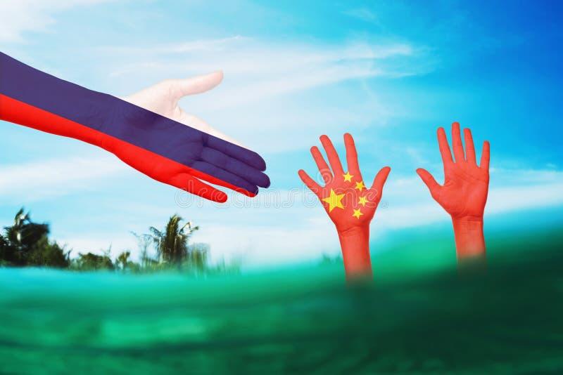 Concetto sul tema dell'assistenza alla Cina da parte di colleghi russi in una situazione difficile Relazioni internazionali immagini stock
