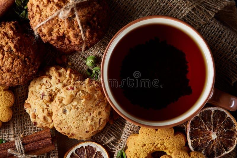 Concetto tradizionale del tè di Natale con una tazza di tè, dei biscotti e delle decorazioni caldi su un fondo di legno, fuoco se fotografie stock