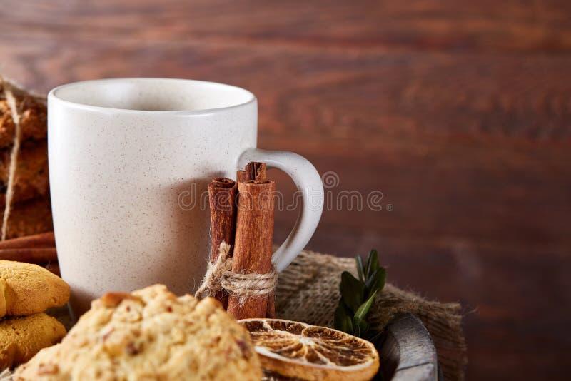 Concetto tradizionale del tè di Natale con una tazza di tè, dei biscotti e delle decorazioni caldi su un fondo di legno, fuoco se fotografia stock libera da diritti