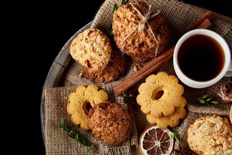 Concetto tradizionale del tè di Natale con una tazza di tè, dei biscotti e delle decorazioni caldi su un fondo di legno, fuoco se fotografia stock