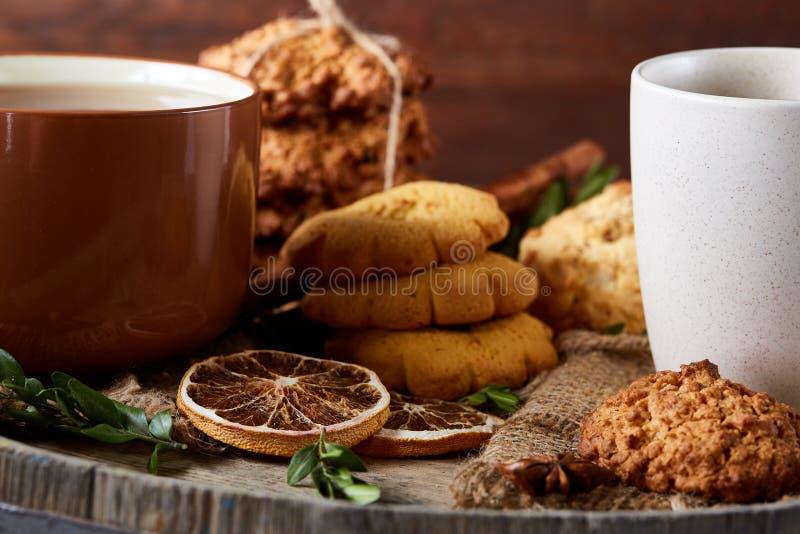 Concetto tradizionale del tè di Natale con una tazza di tè, dei biscotti e delle decorazioni caldi su un fondo di legno, fuoco se immagine stock libera da diritti