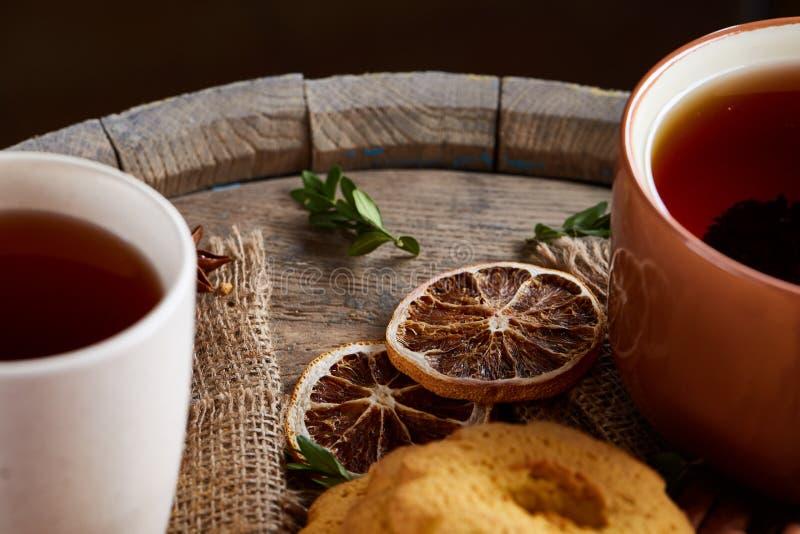 Concetto tradizionale del tè di Natale con una tazza di tè, dei biscotti e delle decorazioni caldi su un fondo di legno, fuoco se immagine stock