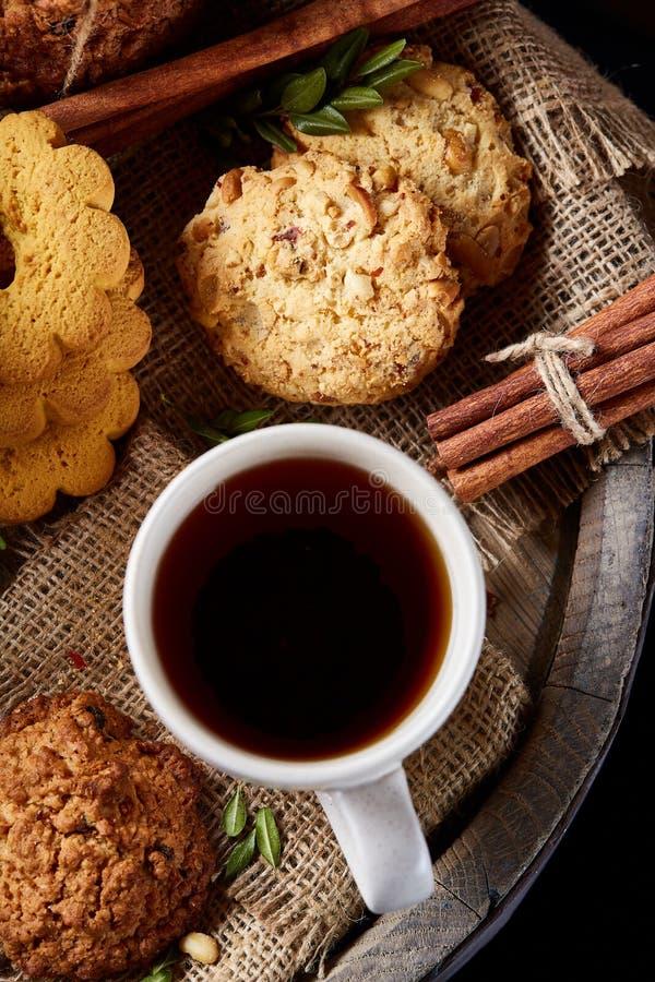 Concetto tradizionale del tè di Natale con una tazza di tè, dei biscotti e delle decorazioni caldi su un fondo di legno, fuoco se fotografie stock libere da diritti