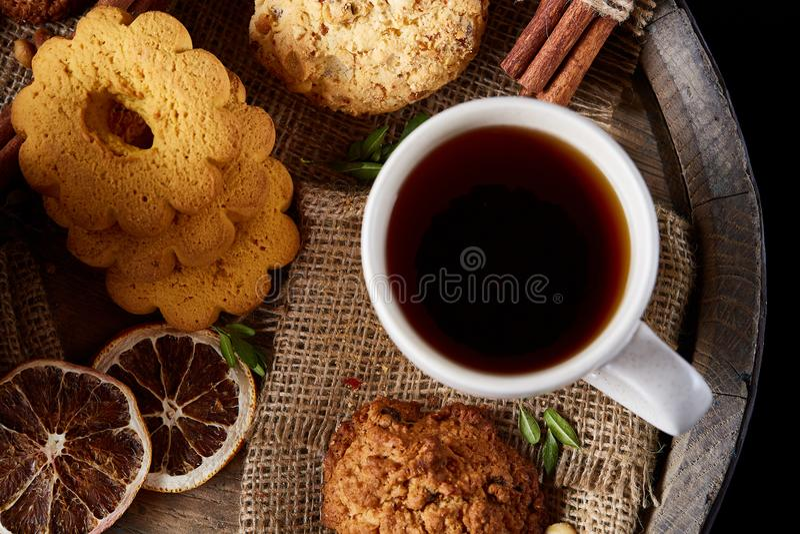 Concetto tradizionale del tè di Natale con una tazza di tè, dei biscotti e delle decorazioni caldi su un fondo di legno, fuoco se immagini stock libere da diritti