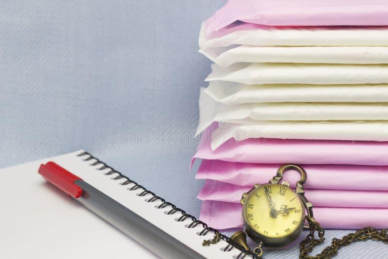 Concezione medica Cuscinetti sanitari di mestruazione, orologio, blocco note, penna rossa per protezione di igiene della donna Pr fotografia stock libera da diritti