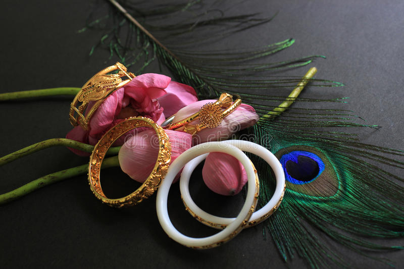 Conch bangle and gold bracelet with pink lotus and peacock feather on black background. Conch bangle and gold bracelet with pink lotus and peacock feather on royalty free stock photography
