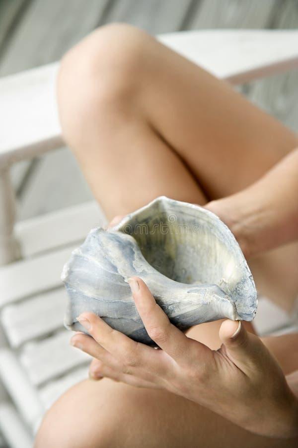 conch girl holding shell 免版税库存图片
