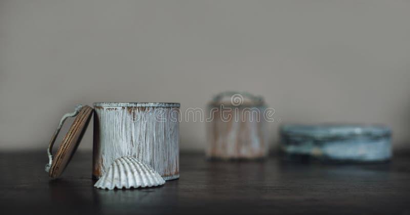 Concha y las pequeñas cajas en la tabla de madera marrón vieja fotos de archivo