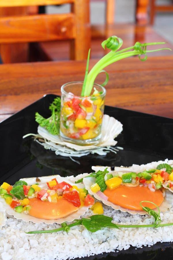 Conchas de peregrino chamuscadas con salsa tropical fotografía de archivo