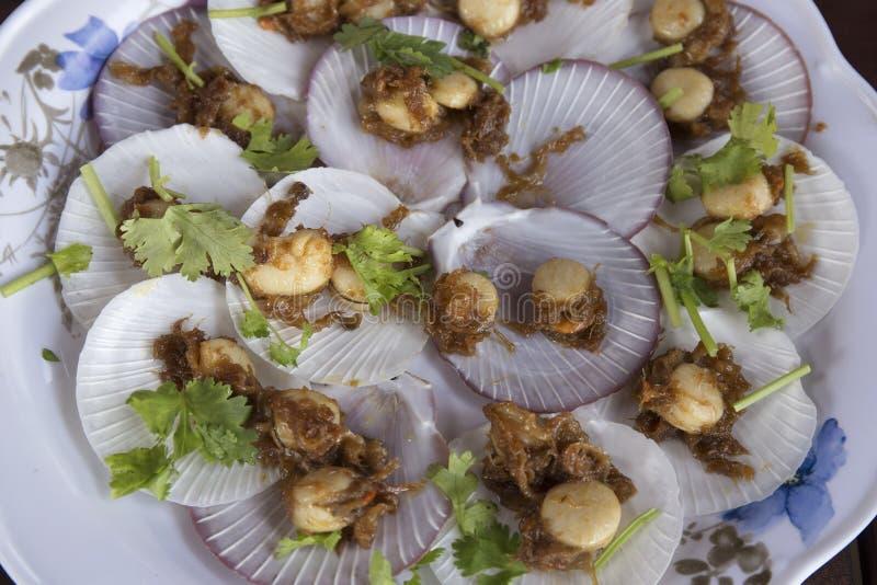 Conchas de peregrino cocidas con mantequilla y ajo en cáscara foto de archivo