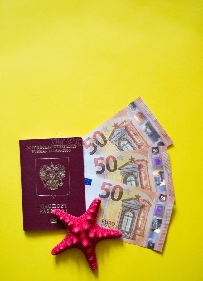 Conchas marinas euro del pasaporte en fondo amarillo como en la playa fotos de archivo