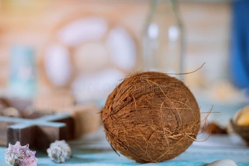 Conchiglie bottiglia e noce di cocco di estate su un fondo blu immagine stock