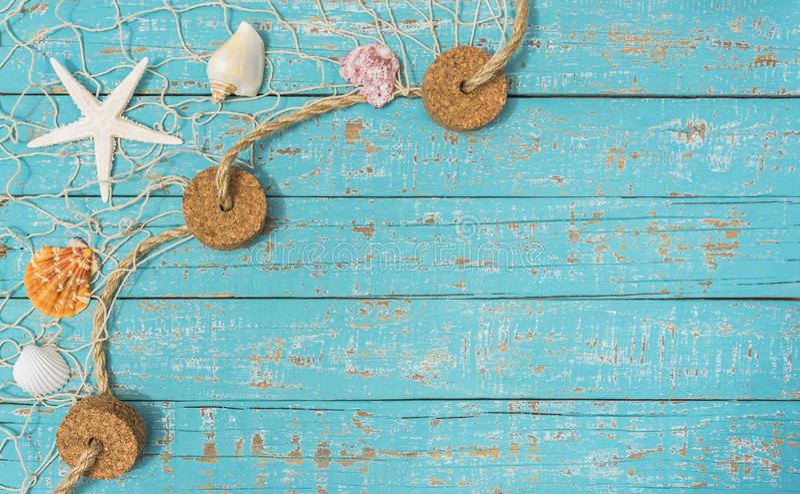 Conchiglie e stella di mare nella rete da pesca su fondo di legno rustico blu-chiaro immagine stock libera da diritti