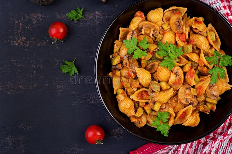 Conchiglie pasta. Italian pasta shells with mushrooms, zucchini and tomato sauce. royalty free stock images