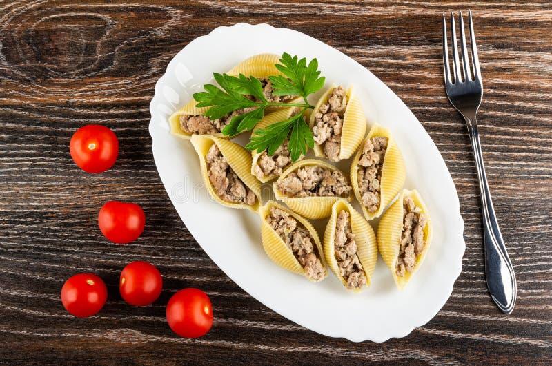 Conchiglie relleno de las pastas, perejil en el plato, tomate, bifurcación en la tabla de madera Visi?n superior fotos de archivo