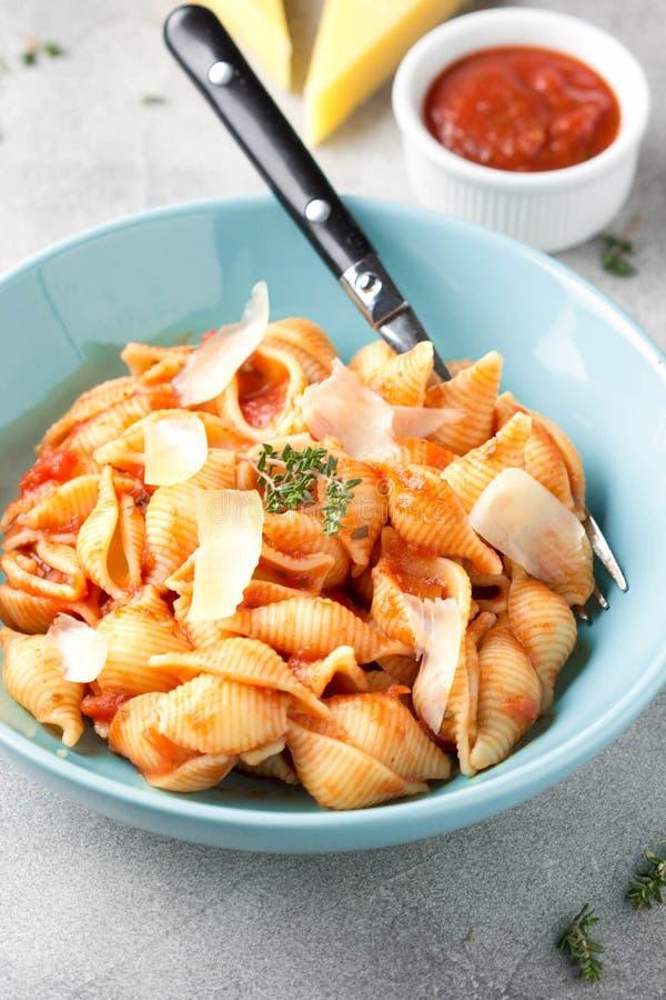 Conchiglioni de pâtes (conchiglie, coquilles) avec la sauce tomate, le parmesan et le thym dans un plat bleu sur un fond gris photo libre de droits