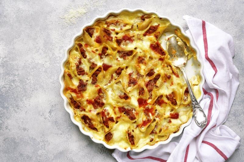 Conchiglioni ha farcito con carne tritata al forno in salsa bolognese T immagini stock
