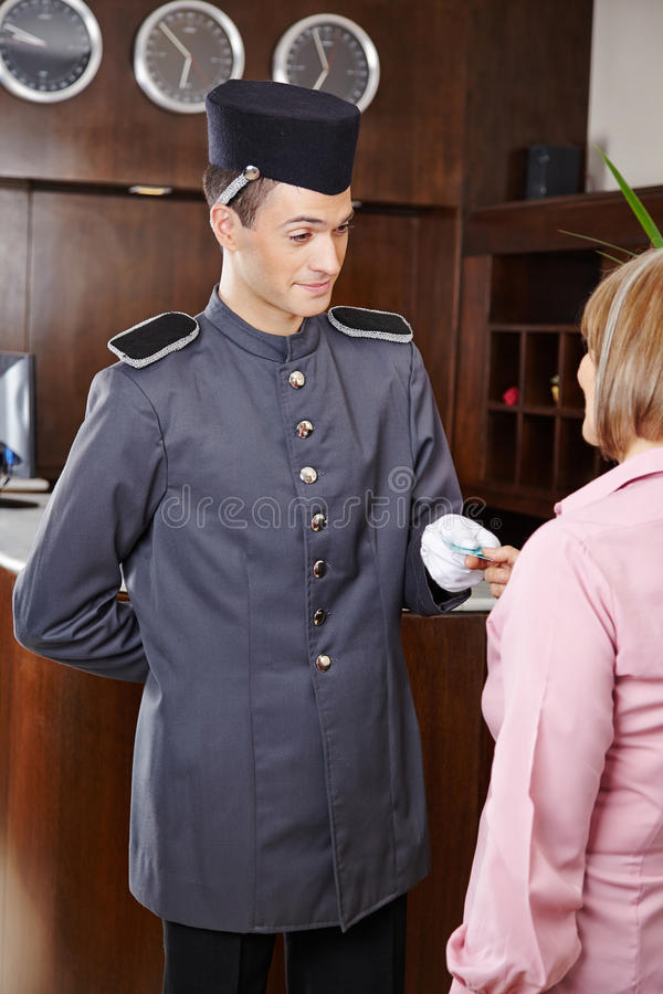 Concierge in hotel giving key card to woman royalty free stock photography