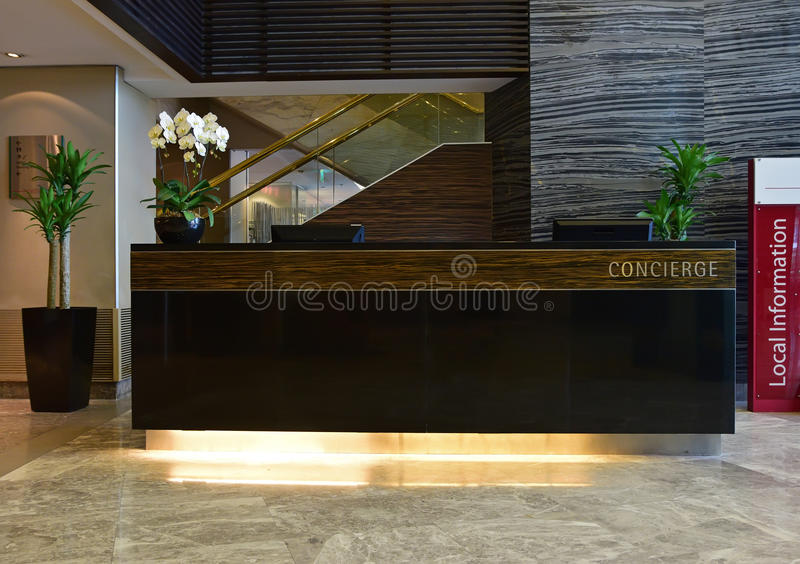 Concierge and Information Desk in a Luxury Hotel. With indoor plants, orchid flower and shining marble around the premise. This is a typical setting of stock photo
