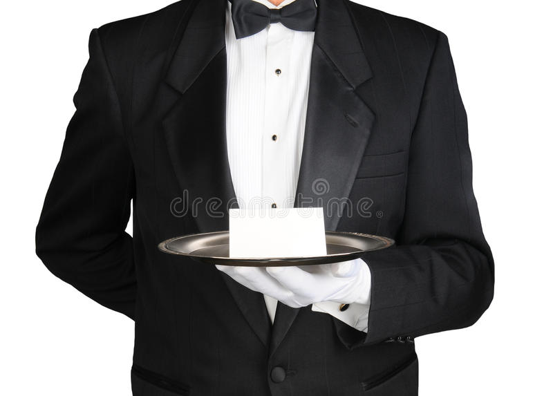 Concierge With Note on Tray. A concierge wearing a tuxedo holding a note card on a silver tray in front of his torso. Man is unrecognizable over white stock photos