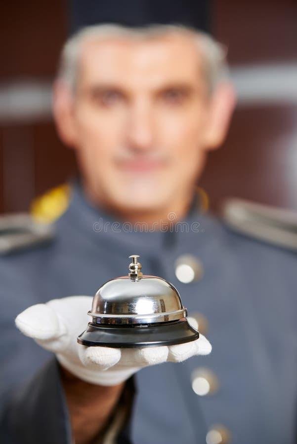 Concierge tenant la cloche d'hôtel en main photographie stock