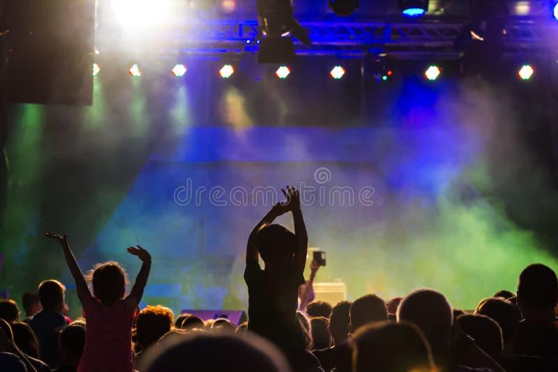 Concierte a la muchedumbre que asiste a un concierto, gente que las siluetas son visibles, retroiluminado por las luces de la eta foto de archivo libre de regalías