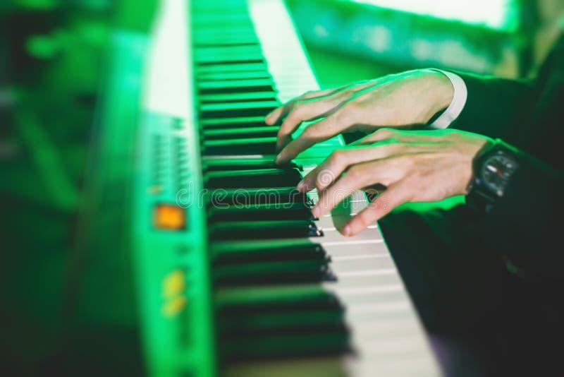 Concierte la opinión un pianista musical del teclado durante la banda de jazz musical que se realiza en el fondo imagenes de archivo