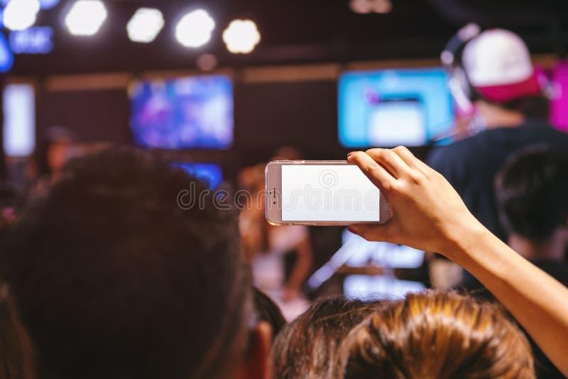 Concierto de la falta de definición del tiro de la foto de la pantalla en blanco del teléfono celular de tenencia de la mano imagen de archivo libre de regalías
