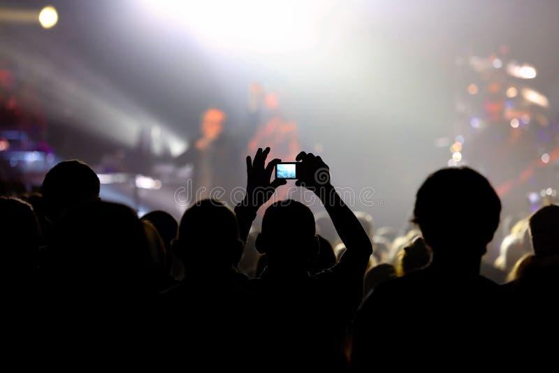 Concierto de la música con la audiencia y el hombre que hacen la foto fotografía de archivo libre de regalías