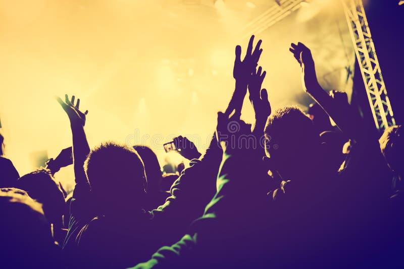 Concierto, partido de disco Gente con las manos para arriba en club de noche imagenes de archivo