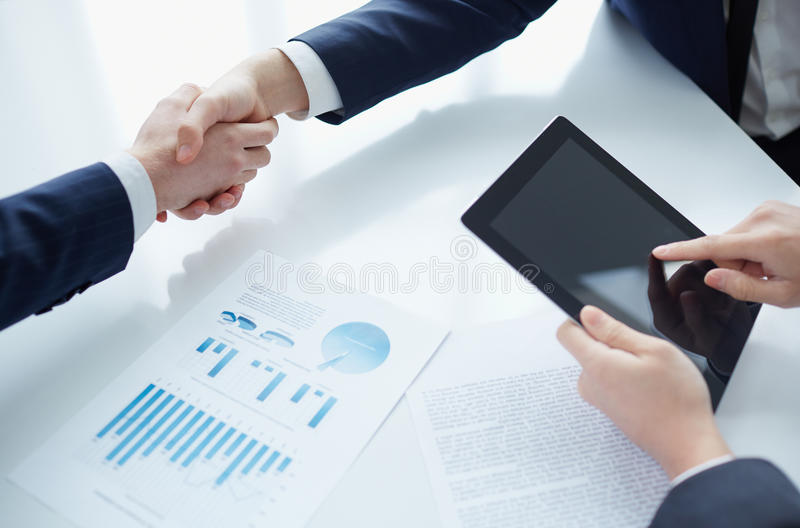 Concluding contract. Managers shaking hands over business plans stock images