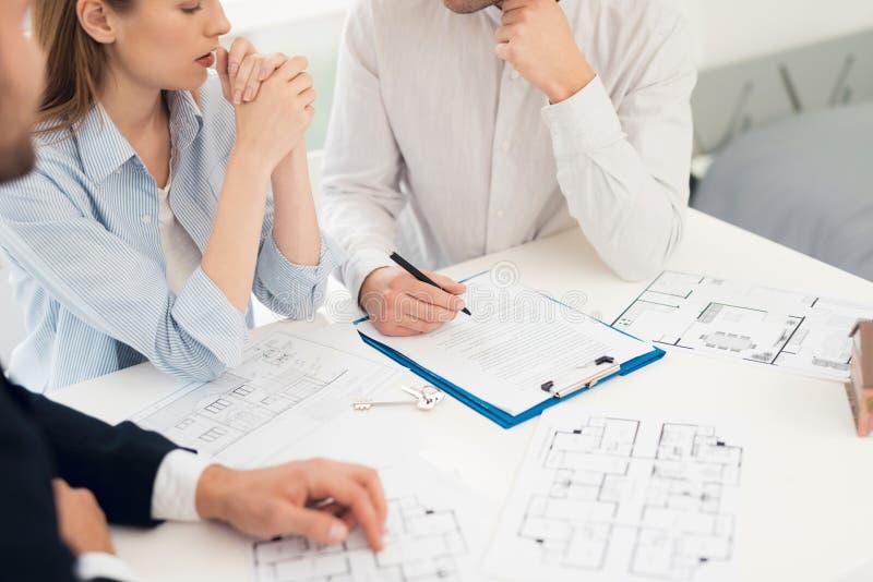 Conclusion d'un contrat pour l'achat de l'ébauche avec l'agent immobilier Photo en gros plan de contrat et d'ébauche photos stock